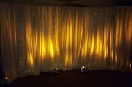 Pipe & Drape Backdrop w/Light Curtain 12' Curved (w/Amber Uplighting)